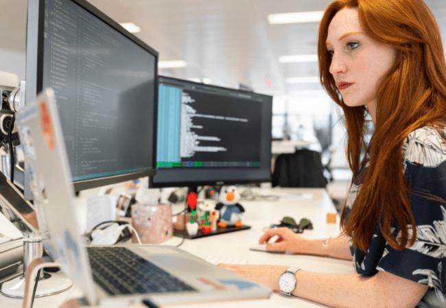 jeune femme devant écran avec lignes de code